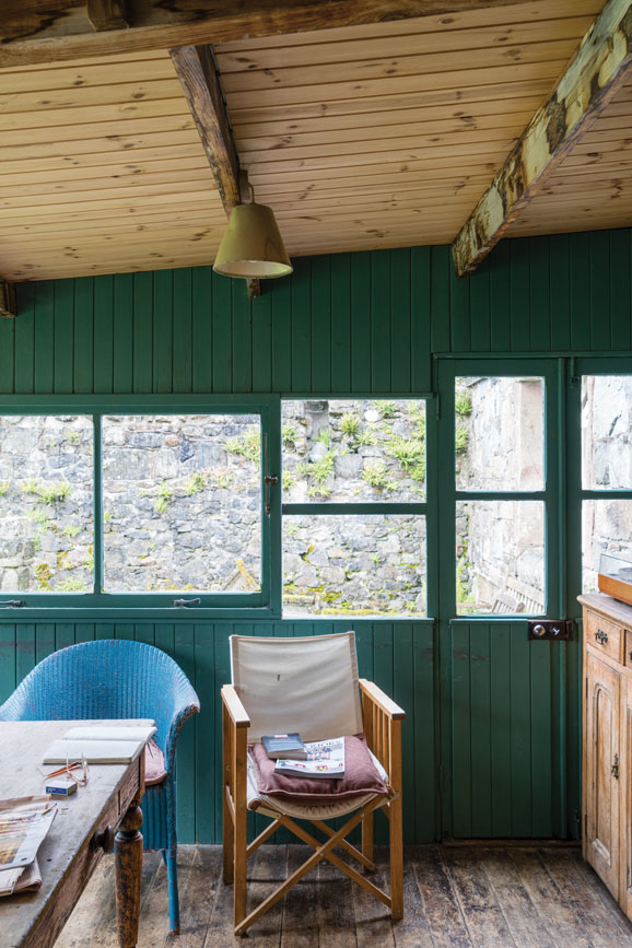 Green summer house with wood panelling painted in Card Room Green