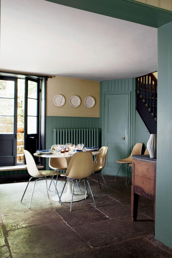 Green and white dining room with wood panelling painted in Card Room Green