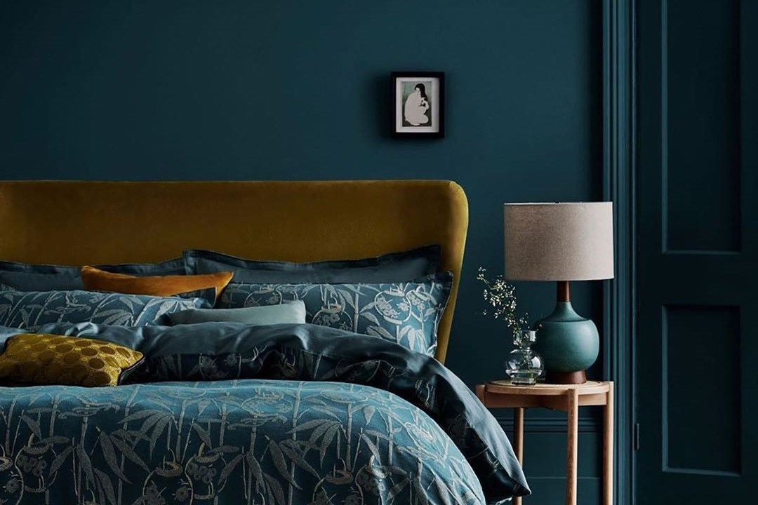 Deep teal coloured bedroom walls and bedding